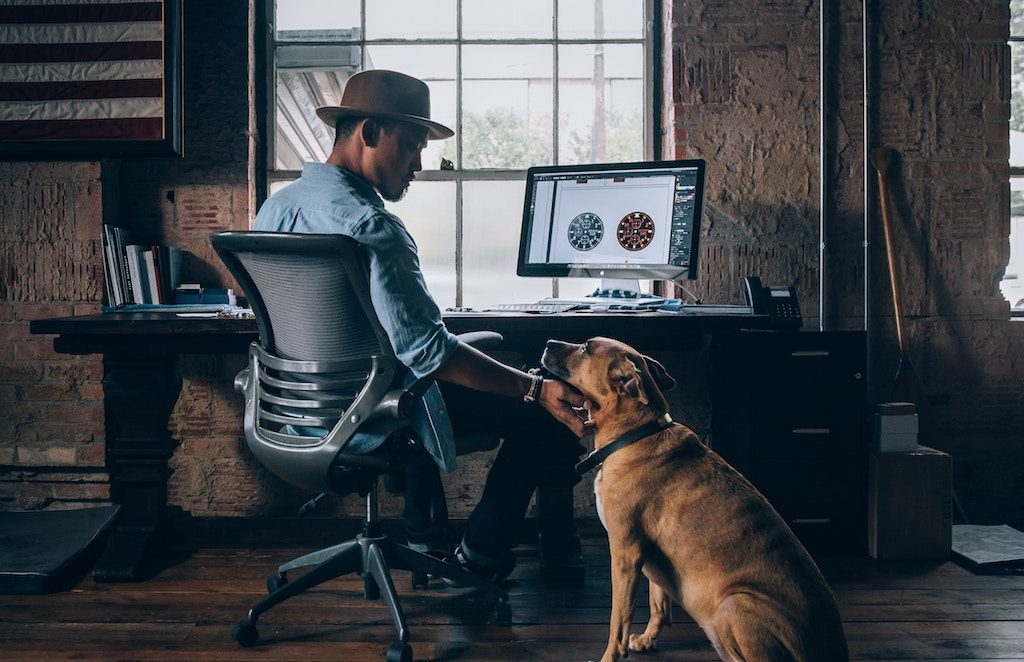 dog next to a man sitting at his desk