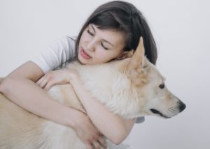 girl hugging a white dog